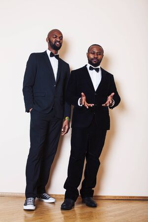 two afro-american businessmen in black suits emotional posing, gesturing, smiling. wearing bow-ties entertaiment stuff