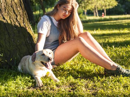 young attractive blond woman playing with her dog in green park at summer, lifestyle people concept Foto de archivo