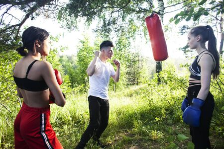 girls fighting boxing outside with coach in green park, sport summer people concept