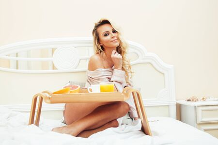 young beauty blond woman having breakfast in bed early sunny morning, princess house interior room, healthy lifestyle concept Standard-Bild