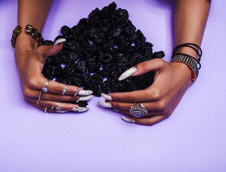 woman hands with long nails manicure holding dry fruits in shape of heart on purple background closeup