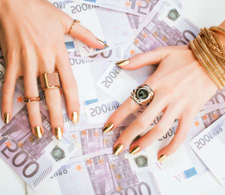 hands of rich woman with golden manicure and many jewelry rings on cash euros Stock fotó