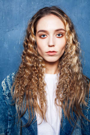 young pretty blond curly girl posing happy smiling on blue background, lifestyle people concept Standard-Bild