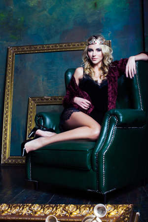 young blond woman wearing crown in fairy luxury interior with empty antique frames total wealth long legs, queen on throne