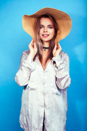 young pretty girl in big hat posing happy smiling on blue background, lifestyle people on summer vacation concept