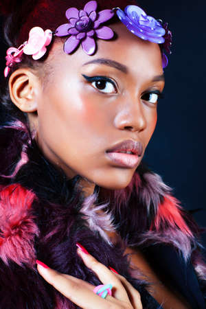 young pretty african american woman in spotted fur coat and flowers jewelry posing on black background 版權商用圖片