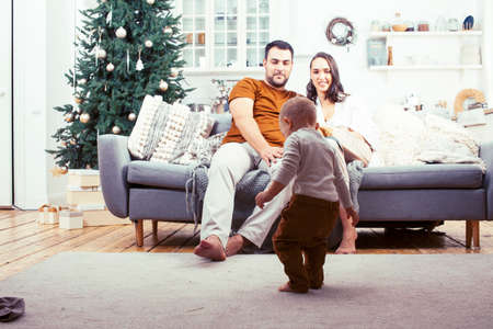 young happy family at home on coach waiting for Christmass with decorated tree, lifestyle people at holiday concept