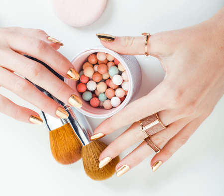 woman hands with golden manicure and many rings holding brushes, makeup artist stuff stylish, pure closeup pink flower rose among cosmetic for makeup Stockfoto