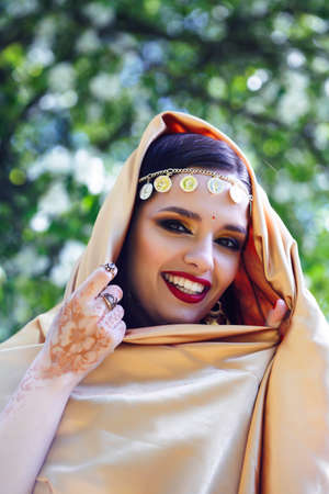 young pretty indian girl in jewelry and veil posing cheerful happy smiling in green park, lifestyle people concept