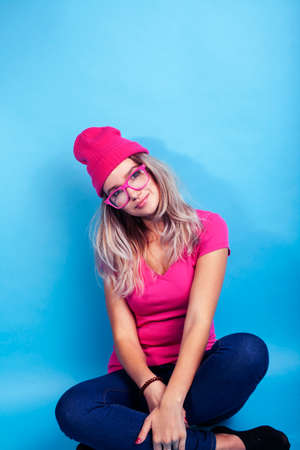 young pretty teenage modern hipster girl posing emotional happy on blue background, wearing pink hat and glasses, lifestyle people concept Stock fotó