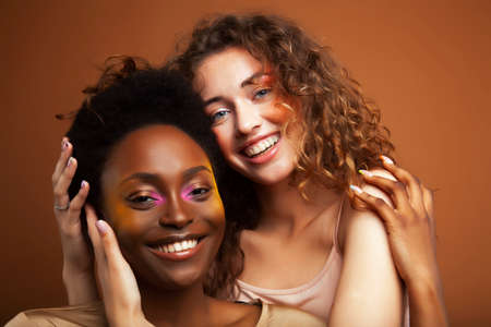 two pretty girls african and caucasian blond posing cheerful together on browm background, etnithity diverse lifestyle people concept
