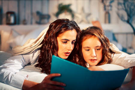 young pretty girls in bed at Christmass morning, happy family smiling lifestyle at holiday reading book Archivio Fotografico