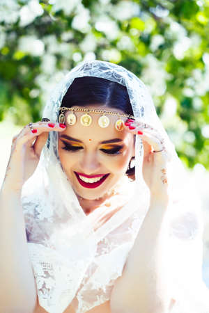 young pretty indian girl in jewelry and veil posing cheerful happy smiling in green park, lifestyle people concept Stock fotó - 152483283