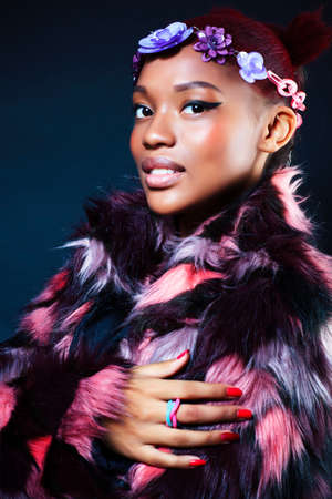 young pretty african american woman in spotted fur coat and flowers jewelry posing on black background Archivio Fotografico