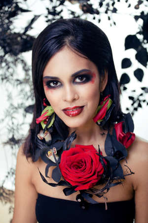 pretty brunette woman with rose jewelry, black and red, bright make up kike a vampire closeup red lips Imagens