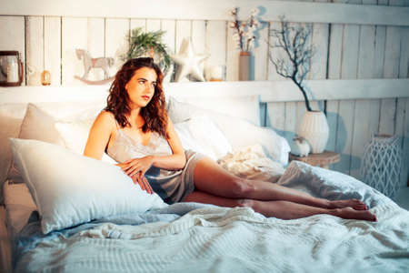 young pretty lady girl posing sexy in vintage hotel bedroom interior, lifestyle rich people concept Archivio Fotografico