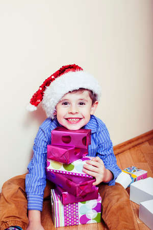 little cute boy with Christmas gifts at home wearing red Santas hat. closeup emotional happy smiling in mess with toys, lifestyle holiday people concept Stock Photo
