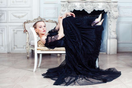 young pretty woman in black lace fashion style dress posing in rich interior of royal hotel room, luxury lifestyle people concept