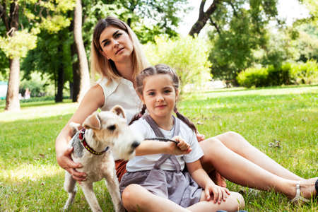 young pretty caucasian mother walking with little cute daughter and dog fox terrier, lifestyle people concept