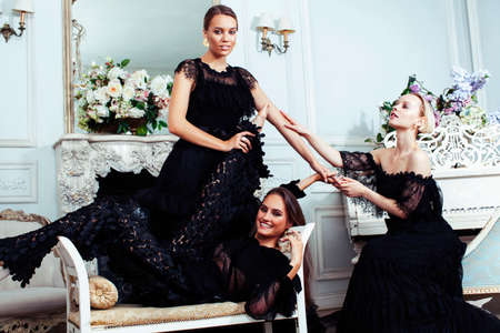 tree young pretty lady in black lace fashion style dress posing in rich interior of royal hotel room, luxury lifestyle people concept