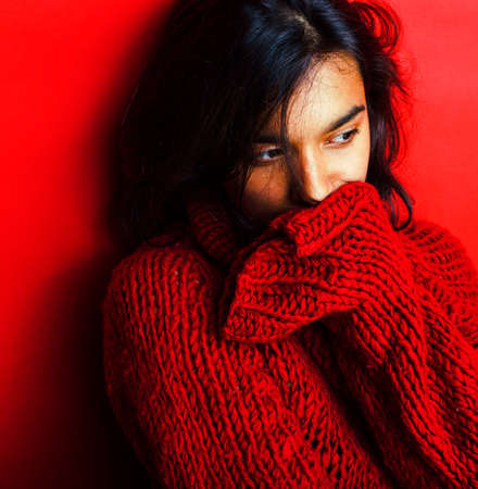 young pretty indian girl in red sweater posing emotional, fashion hipster teenage, lifestyle people concept