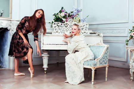 young pretty brunette ballet dancer at piano with blond woman in luxury royal interior, lifestyle rich people concept