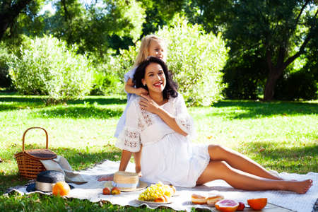 young pretty pregnant brunette woman having fun with her daughter on picnic on green grass in park, lifestyle people concept