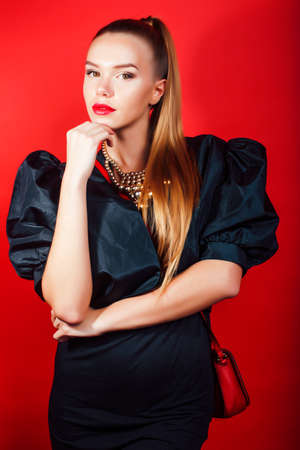 young pretty woman young lady posing on red background wearing gold jewelry, lifestyle people concept