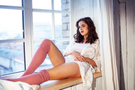 young pretty brunette woman sitting at window at home at morning relaxing, lifestyle people concept