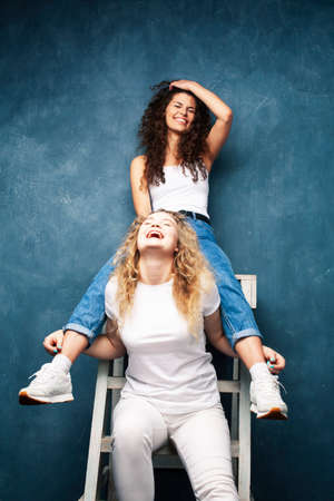 young pretty teenage girls friends with blond and brunette curly hair posing cheerful on blue background, lifestyle people concept 스톡 콘텐츠