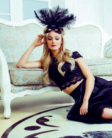 pretty blond woman in luxury palace interior wearing fashion style dress and black mask, lifestyle people concept