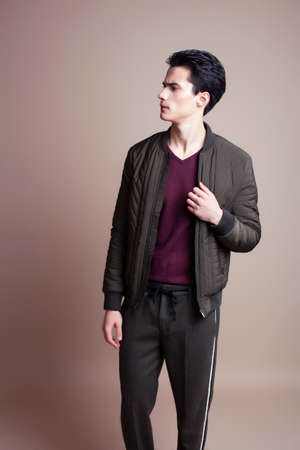 young pretty asian man posing in fashion style on light brown background, lifestyle people concept