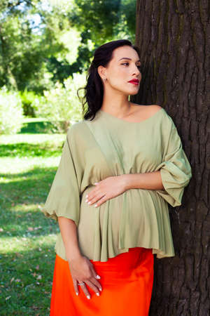 young pretty brunette pregnant woman outdoor in green park happy smiling, lifestyle people concept Reklamní fotografie