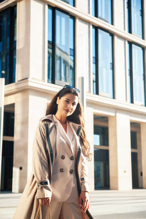 young pretty brunette woman in fashion suit at business building posing cheerful, lifestyle people concept