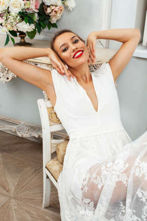 young pretty lady in white lace fashion style dress posing in rich interior of royal hotel room, luxury lifestyle people concept, bride on wedding day