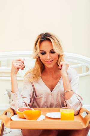 young beauty blond woman having breakfast in bed early sunny morning, princess house interior room, healthy lifestyle concept 스톡 콘텐츠