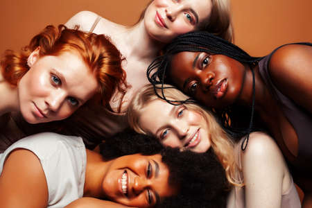 young pretty african and caucasian women posing cheerful together on brown background, lifestyle diverse nationality people concept Stock fotó