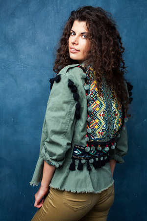 young pretty woman with curly brunette hair posing cheerful on blue background, lifestyle people concept 스톡 콘텐츠