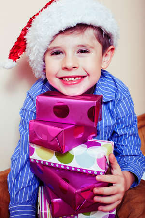 little cute boy with Christmas gifts at home wearing red Santas hat. closeup emotional happy smiling in mess with toys, lifestyle holiday people concept 스톡 콘텐츠