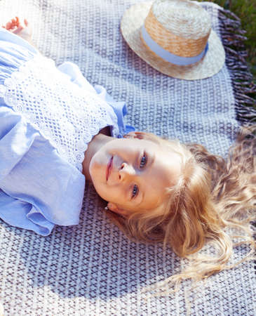 little cute blond girl outside having fun on picnic, lifestyle people concept