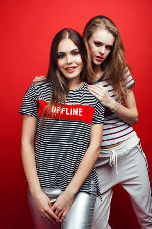 two best friends teenage girls together having fun, posing emotional on red background, lifestyle people concept
