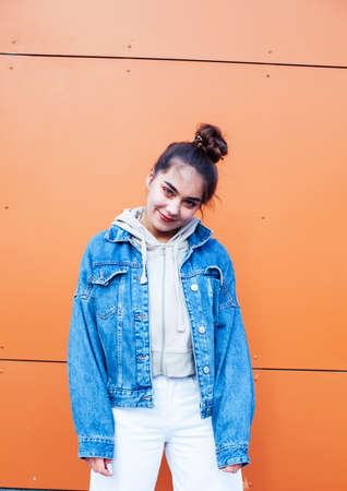 young pretty teenage girl posing cheerful happy smiling wearing street style outside in europe city, lifestyle people concept