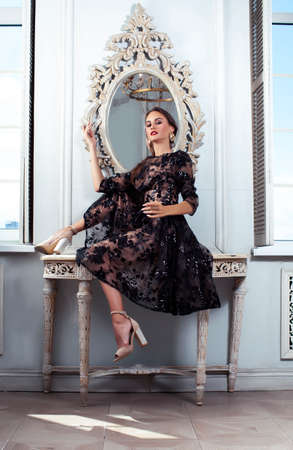 young pretty lady in black lace fashion style dress posing in rich interior of royal hotel room with mirror, luxury lifestyle people concept