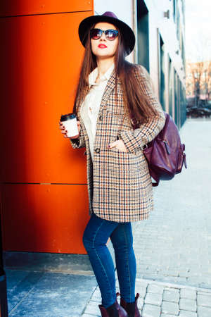 young pretty girl outside in city street with coffee happy smiling wearing hat, lifestyle fashion peopple concept