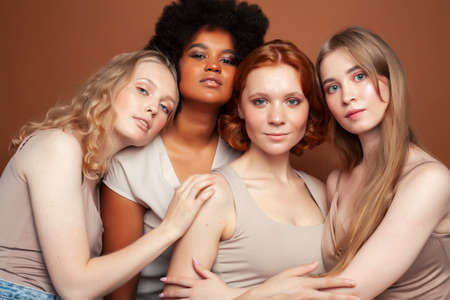 young pretty african and caucasian women posing cheerful together on brown background, lifestyle diverse nationality people concept