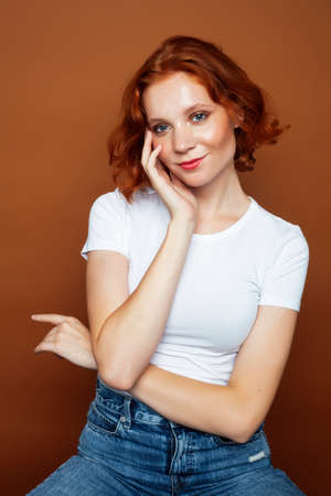 young pretty redhead girl posing cheerful on warm brown background, lifestyle people concept Imagens