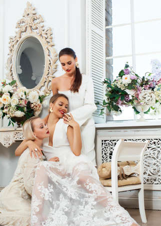 three young pretty lady in white lace fashion style dress posing in rich interior of royal hotel room, luxury lifestyle people concept, bride on wedding day