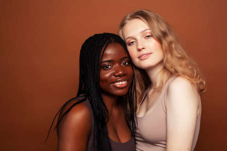 two pretty girls african and caucasian blond posing cheerful together on brown background, ethnicity diverse lifestyle people concept