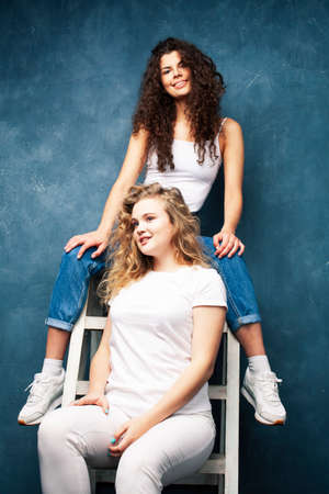 young pretty teenage girls friends with blond and brunette curly hair posing cheerful on blue background, lifestyle people concept Reklamní fotografie