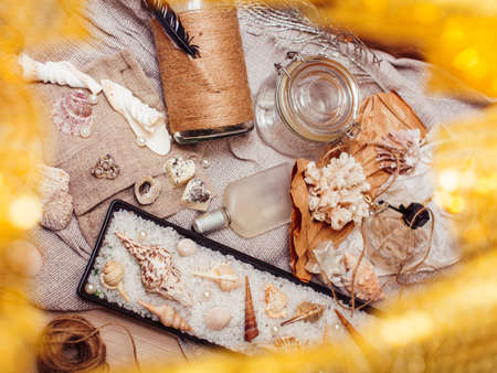 a lot of sea theme in mess like shells, candles, perfume, girl stuff on linen, pretty textured post card view vintage